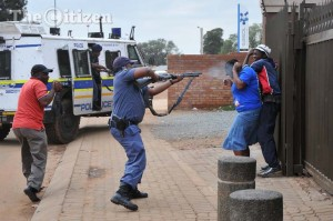 ICASA ordered that this photograph of a police officer firing rubber bullets at unarmed residents during a protest in Bekkersdal over an ANC election campaign be removed from a DA election campaign television advert.