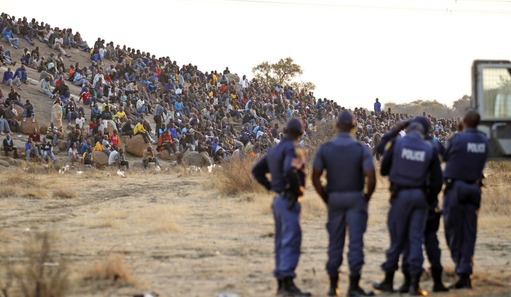 Police keep watch as striking miners gather outside a South African mine in Rustenburg