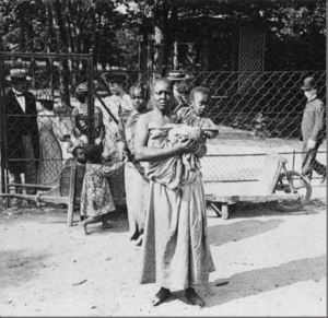 """A Black mother and her child at a """"Negro Village"""" in Germany. This exhibit was known to be very popular and was even visited by conservative statesman Otto von Bismarck."""
