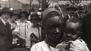 "A Black African mother is shown with her child in a ""Negro Village."""